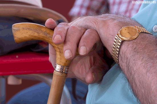 Las manos de un jubilado sostienen un bastón