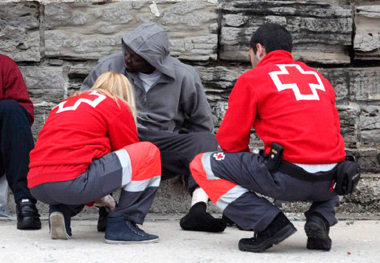 Dos voluntarios de Cruz Roja asisten a una persona inmigrante en su llegada a las costas del Estrecho de Gibraltar