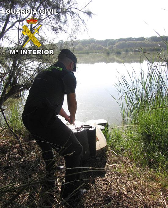 Un agente de la Guardia Civil retira las garrafas de combustible robado sumergidas en el agua.