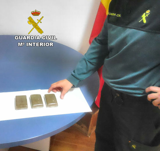 Un agente de la Guardia Civil supervisa la droga aprehendida.