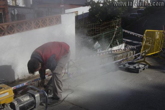 Un obrero de la construcción corta unas losetas.
