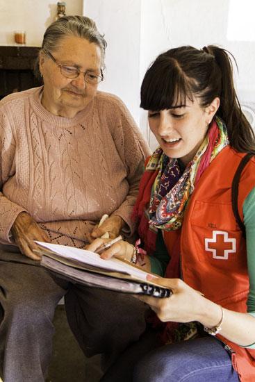 Una voluntaria de Cruz Roja realiza actividades con personas mayores.