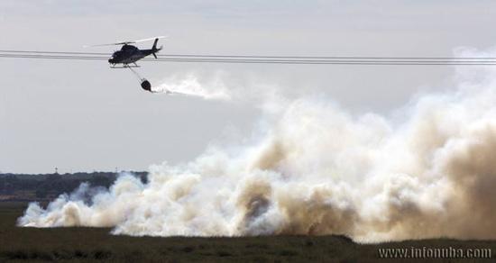un helecoptero descarga en la zona donde se ha producido el incendio el pasado verano