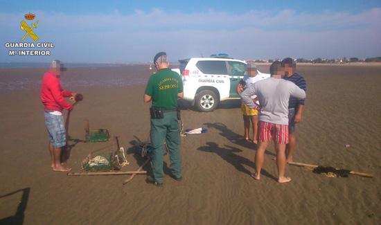 Un agente de la Guardia Civil realiza varias denuncias por marisqueo ilegal.
