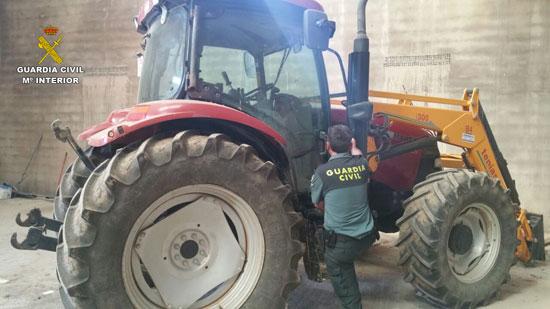 Un agente de la Guardia Civil revisa el tractor sustraído.
