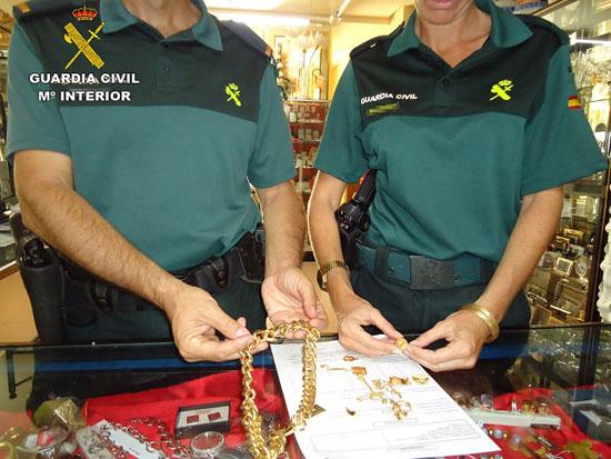 Dos guardias civiles muestran algunos de objetos sustraídos.