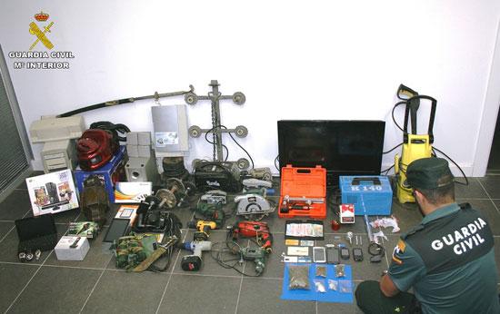 Un agente de la Guardia Civil revisa a droga y el material intervenido en la operación