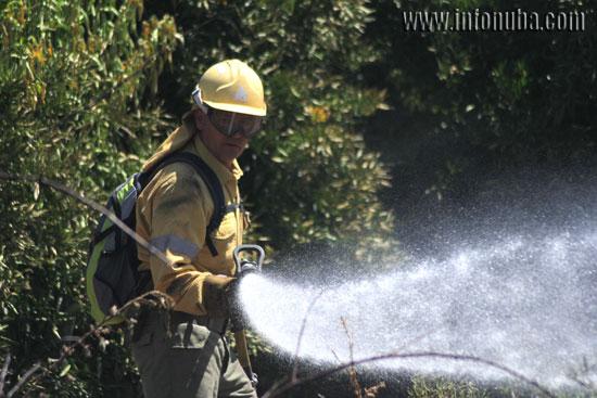 Un bombero realiza labores de extinción en un incendio en Zalamea la Real.