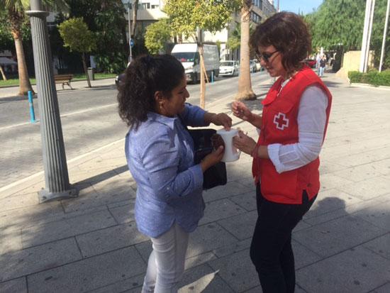 Una ciudadana aporta un donativo en una hucha de la Cruz Roja.