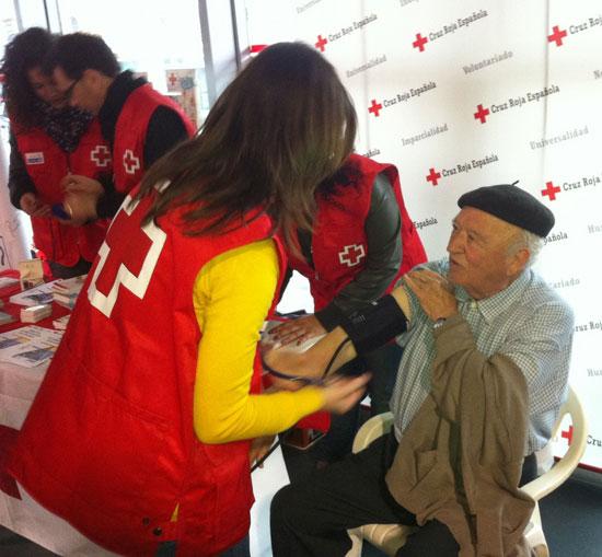 Una voluntaria de Cruz Roja ayuda a una persona mayor a tomarse la tensión arterial.
