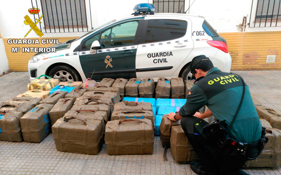 Un agente de la Guardia Civil custodia los fardos incautados.
