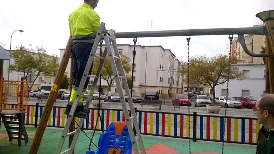 Un operario del Ayuntamiento de Huelva instala el columpio.