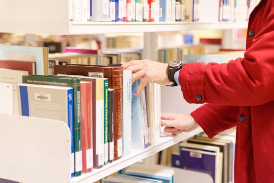Una persona consulta las publicaciones de la Biblioteca de la Universidad de Huelva .