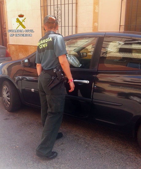 Una agente de la Guardia Civil comprueba un vehículo en la localidad de Isla Cristina.