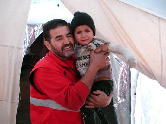 Un voluntario de Cruz Roja junto a un menor.