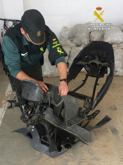 Un agente de la Guardia Civil revisa los restos de la motocicleta sustraída.