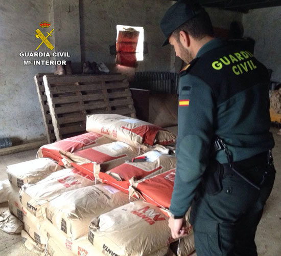 Un agente e de la Guardia Civil comprueba los sacos de pienso robado.