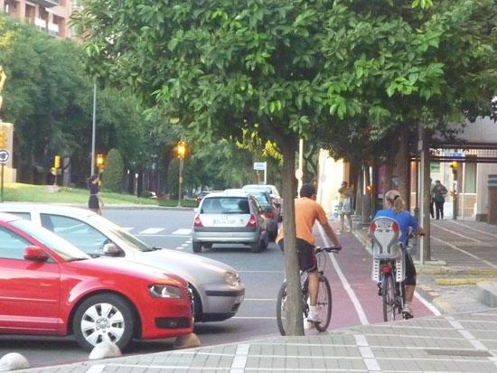 Dos ciclistas pasean por la ciudad de Huelva.
