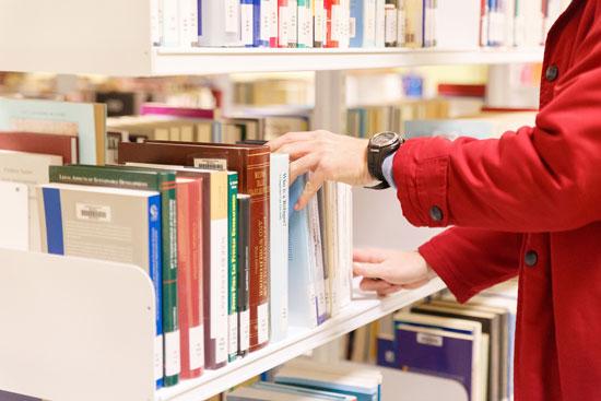 Una persona utiliza los libros de la biblioteca de la UHU.