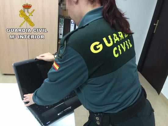Una agente de la Guardia Civil comprueba el estado del ordenador sustraído.