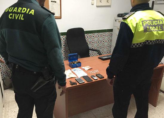 Dos agentes observan la droga y los objetos intervenidos.