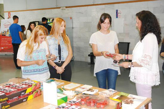 Estudiantes recogen fresas en una mesa informativa.