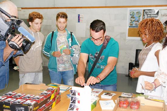 """Imagen de estudiantes en una mesa informativa de la campaña """"Fresas por tabaco""""."""