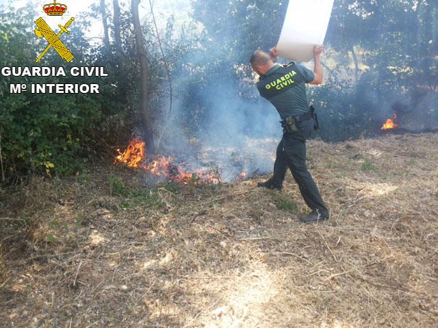 Un agente de la Guardia Civil sofoca el incendio ocurrido en la jornada de ayer en la localidad de Almonaster.