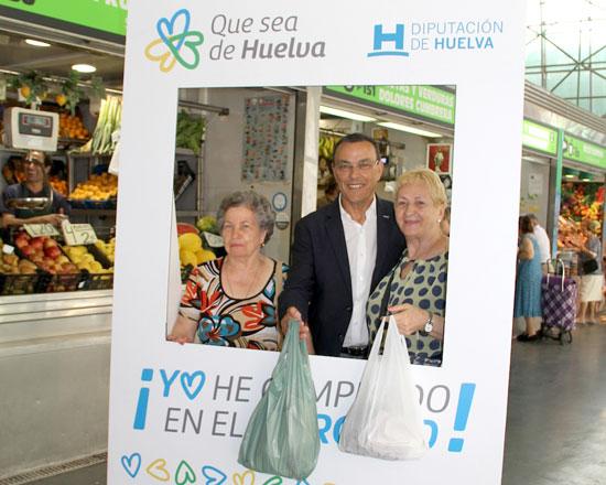 El presidente de la Diputación de Huelva, Ignacio Caraballo, junto a dos vecinas que han realizado hoy su compra en el Mercado de El Carmen.