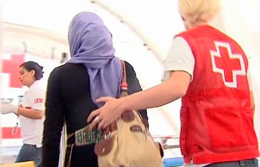 Una voluntaria de Cruz Roja ayuda a una persona refugiada.