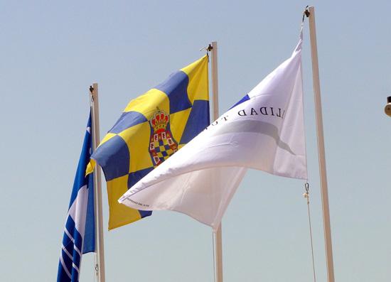 Imagen de la diferentes banderas que ya ondean en la playa del Parador de Mazagón.