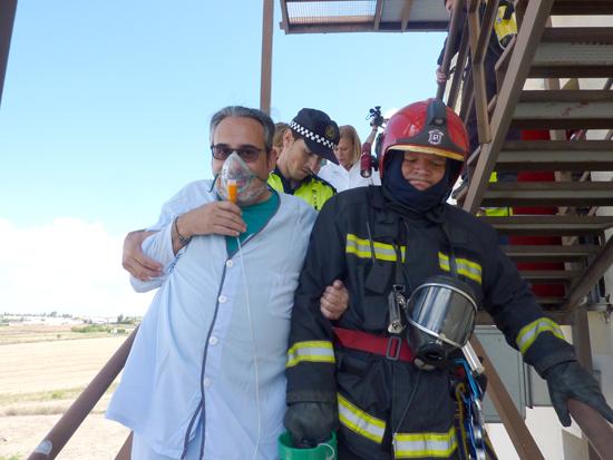 Un bombero ayuda a un paciente en el simulacro de incendio en el Hospital Vázquez Díaz.