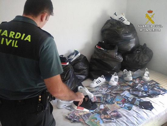 Un agente de la Guardia Civil muestra las diferentes prendas falsificadas.
