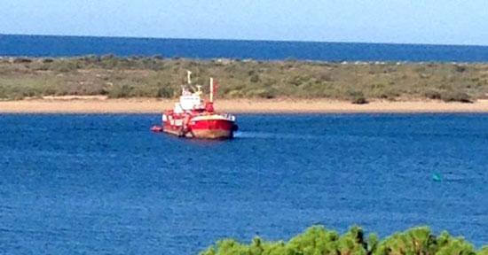 Imagen de una embarcación realizando labores de dragado en la ría del Piedras.