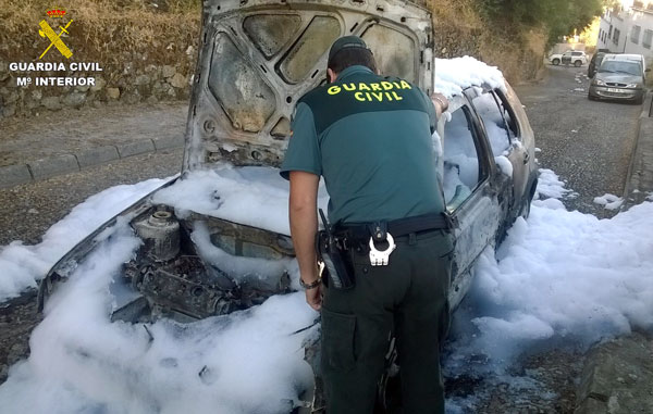 Un agente de la Guardia Civil comprueba los daños en el vehículo afectado.