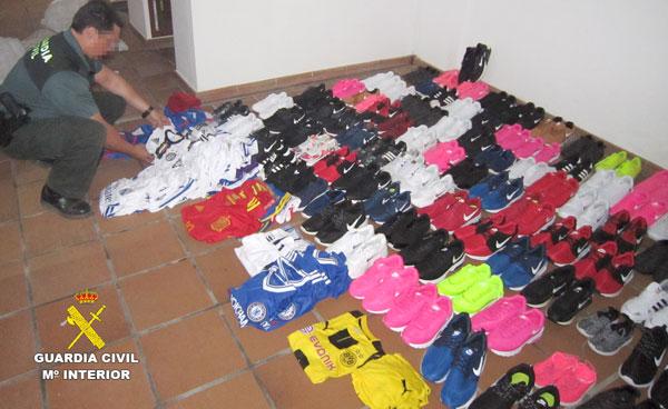 Una agente de la Guardia Civil contabiliza las prendas falsificadas intervenidas.