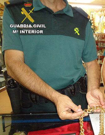 Un agente de la Guardia Civil sostiene uno de los objetos robados.