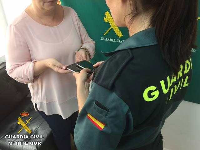 Una agente de la Guardia Civil entrega a su propietaria los móviles sustraídos.