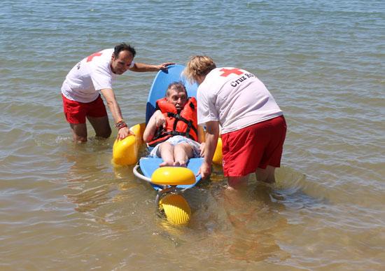 Dos voluntarios de Cruz Roja ayudan a un usuario de anfibuggy.