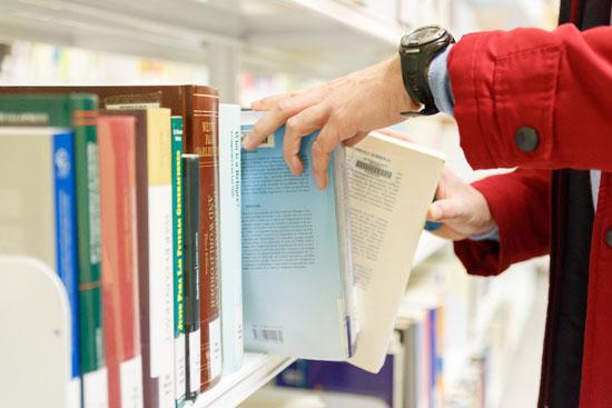 Imagen de una persona consultado publicaciones de la Onubense.