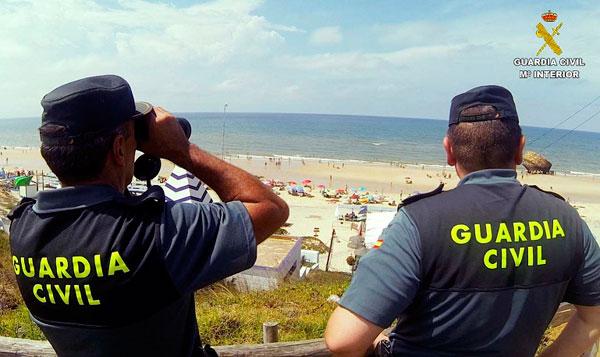 Dos agentes de la Guardia Civil realizan labores de vigilancia en la playa de Matalascañas.