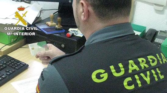 Un agente de la Guardia Civil comprueba la tarjeta de crédito sustraída.