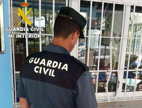 Un agente de la Guardia Civil observa las rejas forzadas del establecimiento.