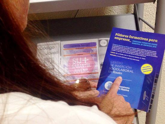 Una persona lee uno de folletos informativos sobre los talleres.