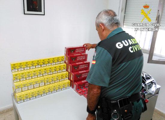 Un agente de la Guardia Civil expone las cajetillas de tabaco incautadas.
