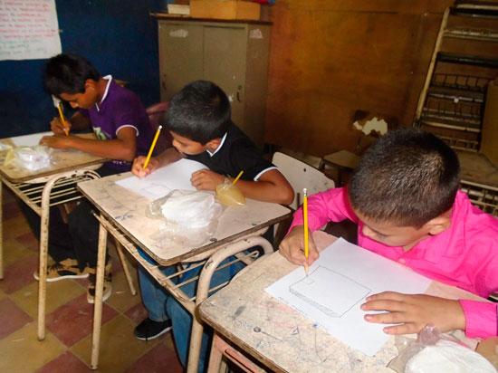 Chicos realizando tareas en la escuela.