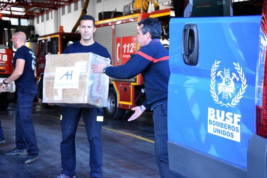 Los bomberos cargan cajas en la furgoneta.
