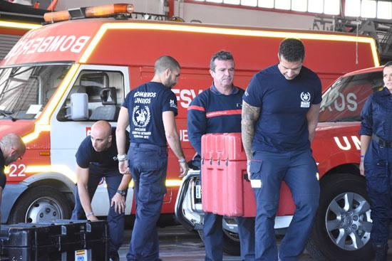 Varios bomberos transportan materiales para su misión en Haití.