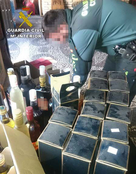 Un agente de la Guardia Civil contabiliza las botellas incautadas.