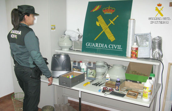 Una agente de Guardia Civil junto a los materiales y droga intervenida.